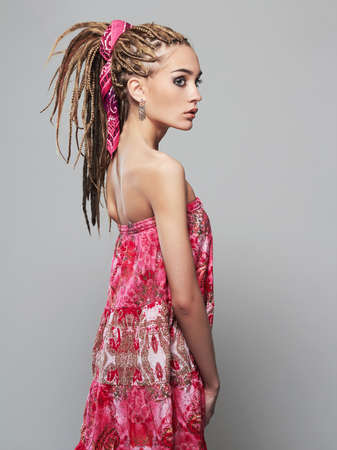 beautiful girl with dreadlocks. pretty young woman with African braids hairstyle. pink dress Stock Photo