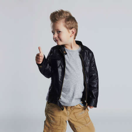 Fashionable child in leather coat.little boy hairstyle. Autumn fashion.funny smiling kid 免版税图像 - 64945518