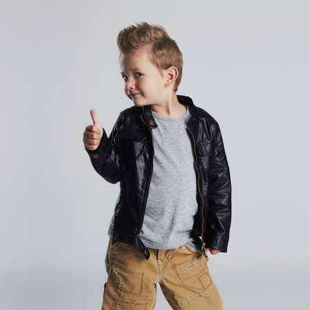 Modieuze kind in leer coat.little jongen kapsel. Autumn fashion.funny glimlachend kind Stockfoto