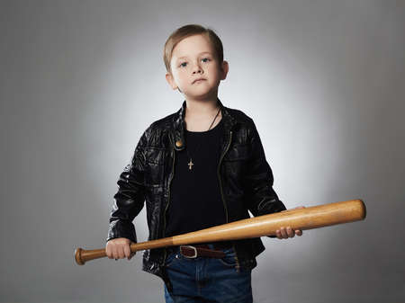 criminal boy with baseball bat.Funny child in leather coat.little thug Banco de Imagens