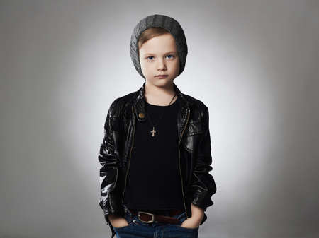 handsome boy.stylish child in winter hat.fashionable kid in leather coat 免版税图像
