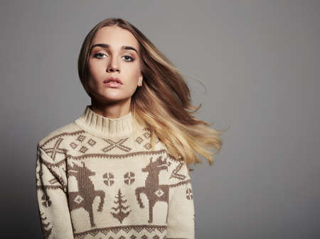 seductress: Beautiful Woman with flying hair in winter pullover. Beauty Blond Girl. Healthy hair