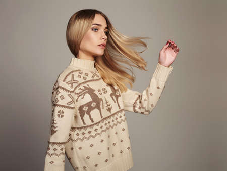 Beautiful Woman with flying hair in winter pullover. Beauty Blond Girl. Healthy hair