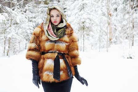 visone: Modello di bellezza nella foresta di inverno. bella giovane donna in moda cappotto di pelliccia, guanti di pelle e sciarpa. lusso siberiano ragazza alla moda