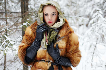 Beauty model girl in winter time. beautiful young Woman in fashionable Fur Coat, leather gloves and scarf. siberian snow around Stock Photo