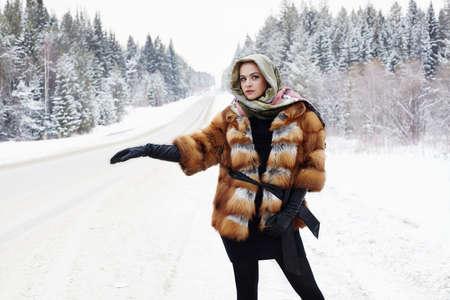 visone: bella ragazza in un cappotto di pelliccia in attesa per l'auto su una strada di inverno nella donna forest.young in moda cappotto di pelliccia, guanti di pelle e sciarpa. tempo di neve