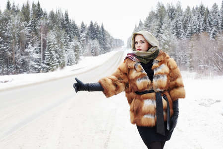 beautiful girl in a fur coat waiting for the car on a winter road in the forest.young Woman in fashionable Fur Coat, leather gloves and scarf. snow time