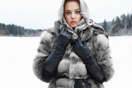 Model van de schoonheid meisje in de winter tijd. mooie jonge vrouw in modieuze bontjas, leren handschoenen en sjaal. siberisch sneeuw rond