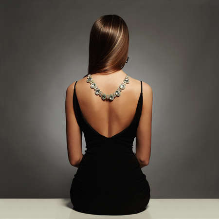 beautiful back of young woman in a black dress.luxury.beauty brunette sitting girl Girl with a necklace on her back.Elegant fashion glamor photo