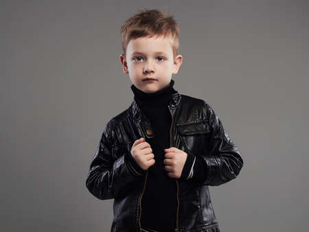 Fashionable child in leather coat.stylish little boy. spring fashion.funny 6 years old kid 免版税图像
