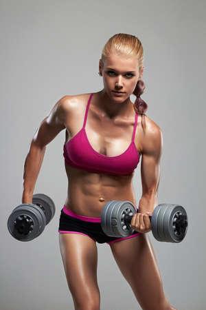 athletische Frau der Eignung, die Muskeln mit Hanteln aufpumpt. schönes blondes Mädchen in der Turnhalle Standard-Bild