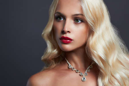 luxury beautiful young woman with healthy curl blond hair. girl with make-up and jewelry Stock Photo
