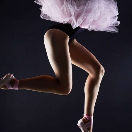 Beautiful female legs.ballet dancer girl.Ballerina is wearing a tutu and pointe shoes