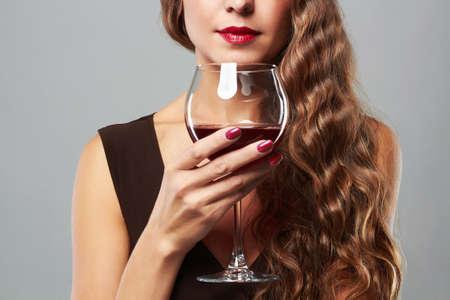 ガラスの赤ワインと美しい女性。巻き毛のヘアスタイル 写真素材