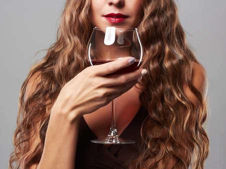 mooie vrouw met glas rode wijn. krullend kapsel