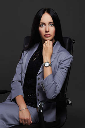 stunning business lady in suit.elegant beautiful business woman sitting on chair Standard-Bild