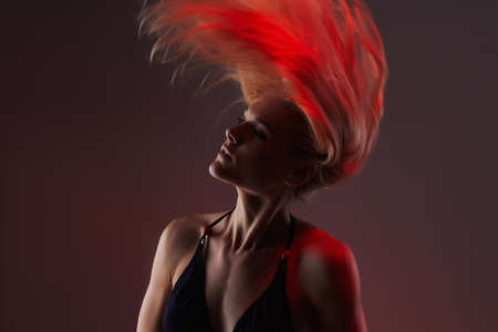 red girl with healthy flying hair.sexy beautiful young woman in the colored spotlights Stock Photo