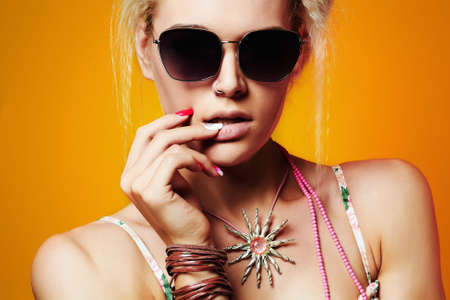 subculture: beautiful teenager girl in sunglasses.beauty young hipster model.orange background