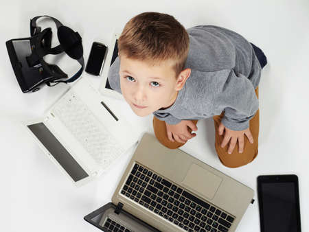 fashionable child with computers, tablets, phones, gadgets around. little boy and new technology