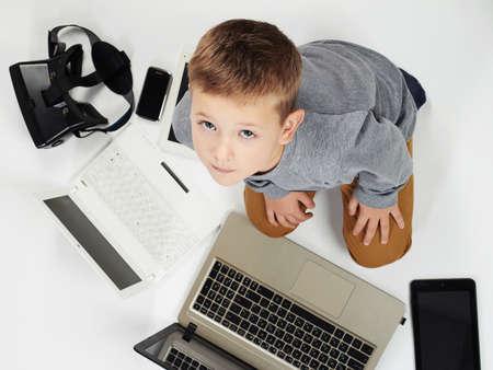 modieus kind met computers, tablets, telefoons, gadgets in de buurt. kleine jongen en nieuwe technologie