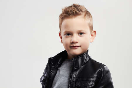 Fashionable child in leather coat.stylish little boy with trendy haircut Banco de Imagens
