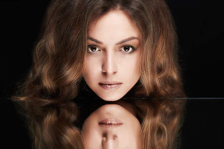 Beautiful woman with mirror reflection. Beauty model girl with make-up and curly hair Imagens