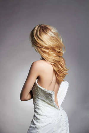 beautiful back.blonde bride woman in unbuttoned wedding dress.fashion style Bride girl with flying hair