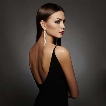 beautiful back of young woman in sexy dress.luxury beauty girl in a black sexy dress with open back wearing jewelry Stock Photo