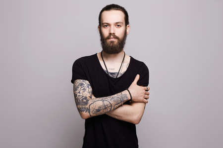 handsome bearded man.Brutal hipster boy with tattoo Imagens