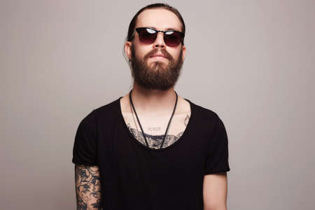 タトゥーとサングラスのファッショナブルなハンサムな男。おしゃれなメガネで残忍なひげを生やしたセクシーな男の子