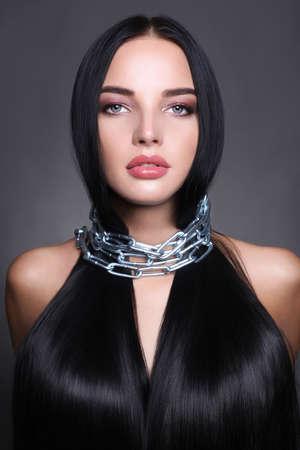 Schöne Brunettefrau mit dem langen gesunden Haar in der Stahlkette. Schönheitsmake-up und glänzendes Haarmädchen