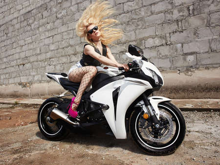Sexy woman in sunglasses sitting on a sport motorcycle.fashion blond rider girl on a motorbike