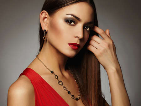 young beautiful sexy woman in red dress and jewelry.Beauty brunette girl with red lips make-up