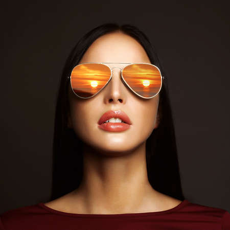 beautiful young woman with sunglasses.Reflection of the sunset in womens glasses