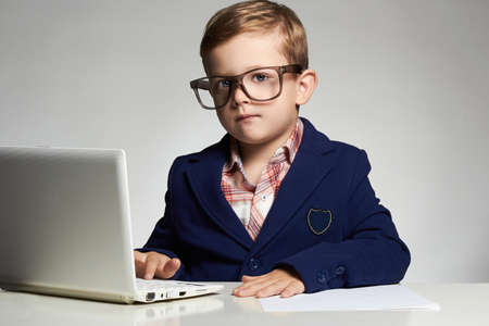 Young businessman using a laptop.little handsome boy in office.modern child