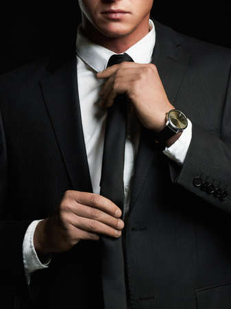 businessman adjusting his tie. young man in suit Stock Photo