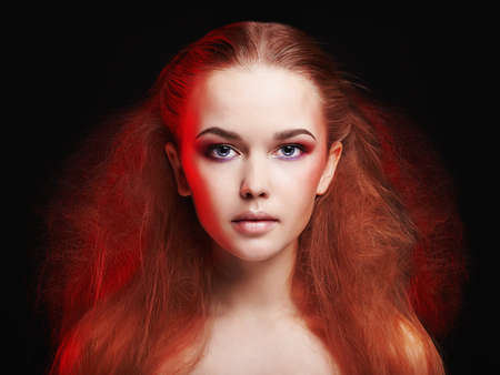 beauty Young woman with make-up and red hair.Beautiful Girl with fashion Three-dimensional hairdo