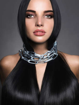 Beautiful young woman in steel chain. beauty make-up and shining hair girl