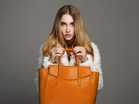 Winter beautiful Woman with orange Handbag.Beauty Fashion Girl in fur