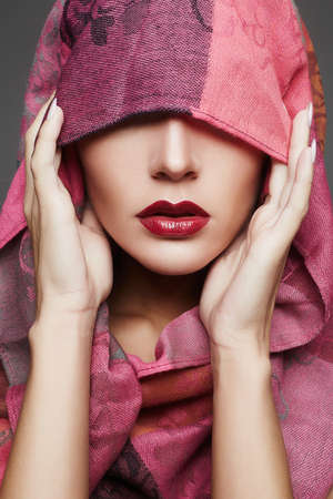 beautiful woman covers her face with a colored cloth.red lips girl.fashion islamic style woman in pink Stock Photo