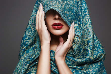 beautiful woman covers her face with a colored cloth.red lips girl.fashion islamic style woman 免版税图像