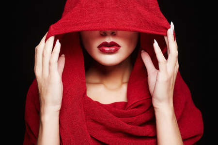 beautiful woman covers her face with a red cloth.red lips girl under hood.fashion islamic style woman