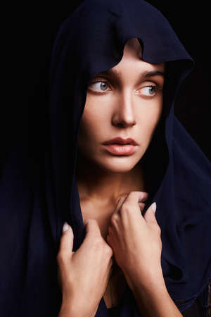 praying beautiful girl with head covering. religious young woman in hood Stock Photo