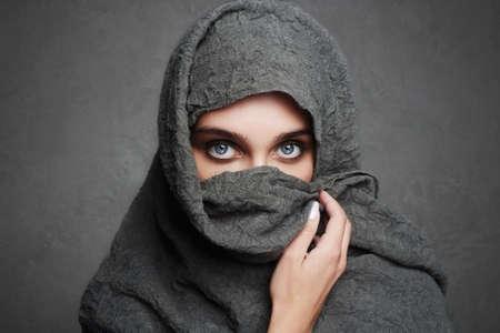 beautiful arab woman covers her face with hi jab.fashionable arabian style girl.beauty portrait.beautiful eyes Stock Photo