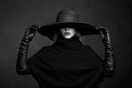 Beautiful woman in hat and leather gloves.fashion model girl.halloween witch