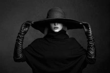 Piękna kobieta w kapeluszu i skórzanych rękawiczkach. Dziewczyna modelka. Halloweenowa czarownica