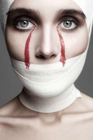 할로윈 스타일 여성의 얼굴 bandage.girl 피 묻은 눈물에 싸여. 아름 다운 젊은 여자 패션 뷰티 흑백 초상화