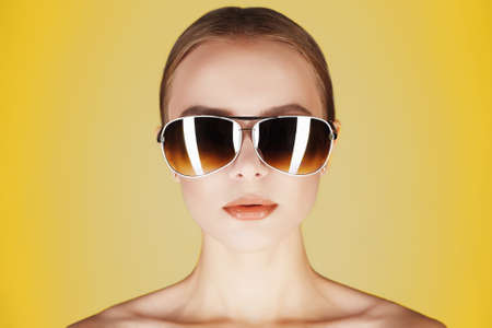 stylish beautiful young woman in sunglasses.fashionable girl in glasses standing by the yellow background