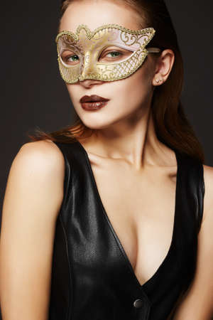 beautiful young woman in mask.Beauty red hair girl in Carnival Mask and sexual leather dress.Masquerade