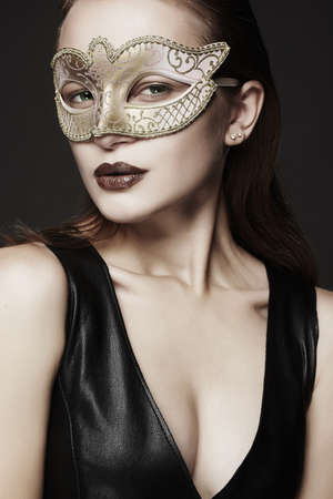 beautiful young woman in mask.Beauty girl in Carnival Mask and sexual leather dress.Masquerade
